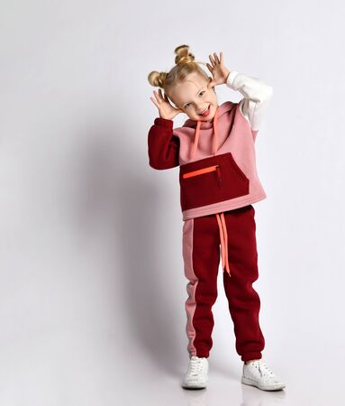 Little blonde lady with buns hairstyle, in colorful sport suit, sneakers. She making faces, fooling, showing tongue, posing isolated on white. Childhood, fashion, advertising. Close up, copy space Zdjęcie Seryjne
