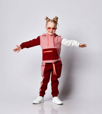 Cute blonde model with bun hairstyle, in sunglasses and a colorful tracksuit. She is posing in full growth posing isolated on white. Childhood, fashion, advertising.