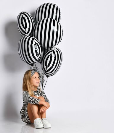 Little lady in zebra-print dress, headband and sneakers. She is smiling, sitting on floor, posing with striped balloons isolated on white. Childhood, fashion, advertising. Close up, copy space
