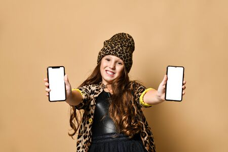 Young happy plus size girl model in stylish leopard colored casual clothing, accessories and black skirt standing, holding two smartphones in hands and smiling over pastel yellow wall background