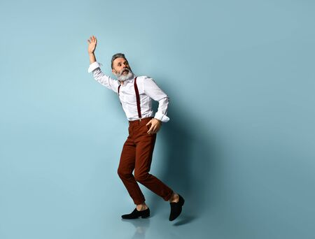 Gray-haired, bearded man in white shirt, brown pants and suspenders, black loafers. He runs looking back, raised his hand up, posing on blue background. Fashion and style. Full length, copy space