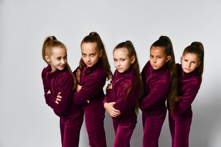 Group of young smiling girls gymnasts in dark red velvet sport costumes standing and posing over white background. Rhytmhic gimnastics beauty and team sport cocnept