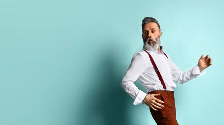 Gray-haired, bearded male in white shirt, brown pants and suspenders, black loafers. He runs looking back, posing sideways against blue studio background. Fashion and style. Full length, copy space Stockfoto