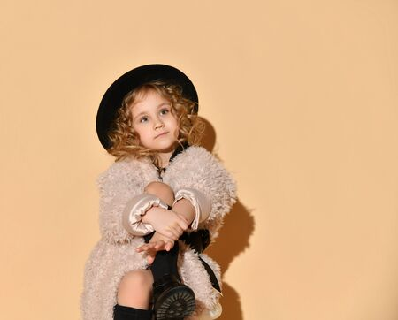 Blonde curly little lady in pink faux fur coat, black hat and boots. She hugged her crossed legs while sitting against beige studio background. Childhood, fashion, advertising. Close up, copy space Foto de archivo