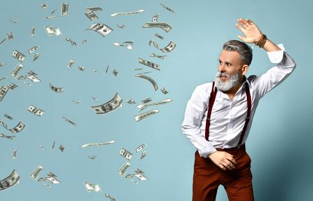 Gray-haired, aged man in white shirt, brown pants and suspenders, bracelet. He looks scared, swatting at hundred dollar bills which pursuing him, blue studio background. Close up, copy space