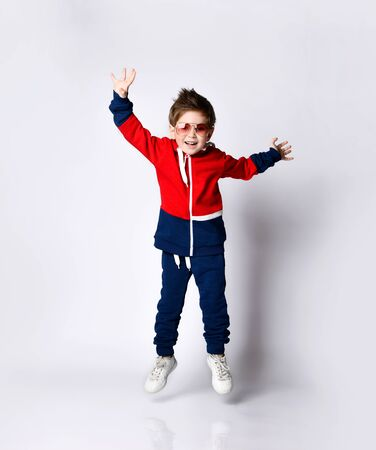 Little blond kid in blue and red tracksuit, sneakers, sunglasses. Smiling, jumping up with raised hands while posing isolated on white. Childhood, fashion, advertising, sport. Full length, copy space