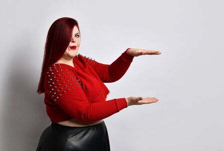 Big red-haired girl in a red studded top, black leather skirt. She looks surprised, holding or showing something big, posing from the side, isolated on white. Fashion Style. Close copy space
