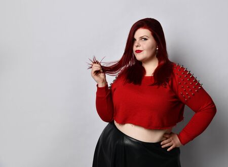 Fat redhead lady in a red studded top, black leather skirt and earrings. She directly touches her hair, puts a hand on her waist and poses on a white background. Fashionable style. Close copy space