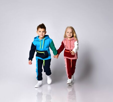 Children, boy and girl, in colorful sport suits and sneakers. They are holding hands, running, isolated on white studio background. Childhood, fashion, advertising. Full length, copy space