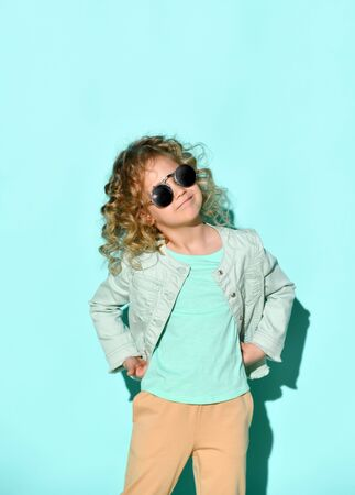 cute little curly girl with black opaque glasses on her face is standing with her hands on her hips with a business look. Studio shot isolated on turquoise. Casual style, Zdjęcie Seryjne