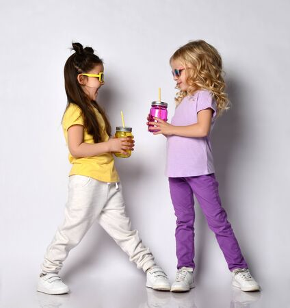 Two little gorgeous girls in sunglasses, colorful casual clothes. They holding cocktail bottles, smiling, looking at each other, posing isolated on white. Childhood, fashion. Full length, copy space Zdjęcie Seryjne