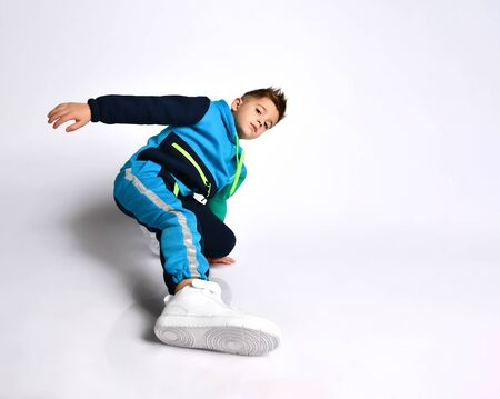 Little man in colorful tracksuit, sneakers. He performing exercises or kick by his leg, posing isolated on white background. Childhood, fashion, advertising and sport. Full length, copy space