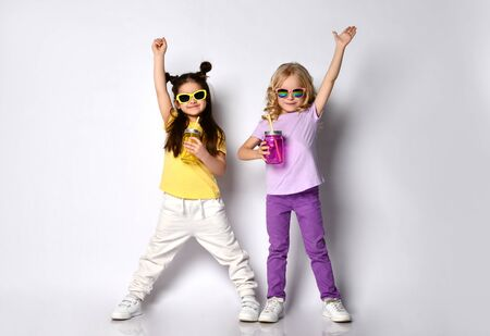 Two little gorgeous females in sunglasses, colorful casual clothes. They holding cocktail bottles, smiling, raised hands up, posing isolated on white. Childhood, fashion. Full length, copy space Zdjęcie Seryjne