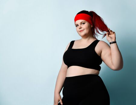 Concentrated plus-size girl in black sportswear stands looking aside thoughtfully, touching her face and holding ponytail in hand on blue background. Fitness, diet, body positive. Close up view