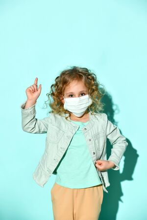 Little blond curly girl in a t-shirt, denim jacket and beige pants. She is in a medical mask, pointing to something, posing on a turquoise background. Coronavirus. Pandemic COVID-19. Attention Zdjęcie Seryjne