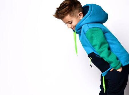 Little bro in colorful tracksuit. Smiling, put hands in pockets, posing sideways isolated on white studio background. Childhood, fashion, advertising and sport concept. Close up, copy space