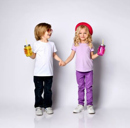 Little girl and boy in colorful casual clothes, sunglasses and hat. Smiling, holding hands, yellow and pink cocktail bottles. Posing isolated on white. Childhood, fashion. Full length, copy space