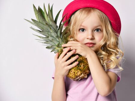 Little blonde kid in red hat and purple blouse. She is looking at you and hugging pineapple, posing isolated on white studio background. Childhood, healthy nutrition, advertising. Close up, copy space