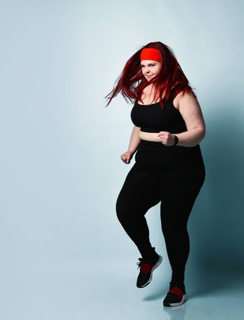 Active energetic overweight girl smiling and jogging in place on light blue background. Fitness, sport, diet, physical activity, body positive, weight loss concept. Full length portrait, copy space