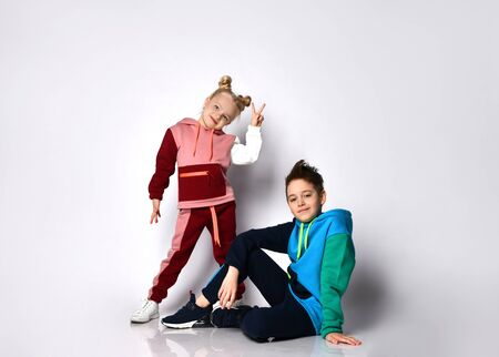 Children, brother and sister, in colorful tracksuits and sneakers. They looking at each other, smiling, posing isolated on white. Childhood, fashion, advertising and sport. Full length, copy space