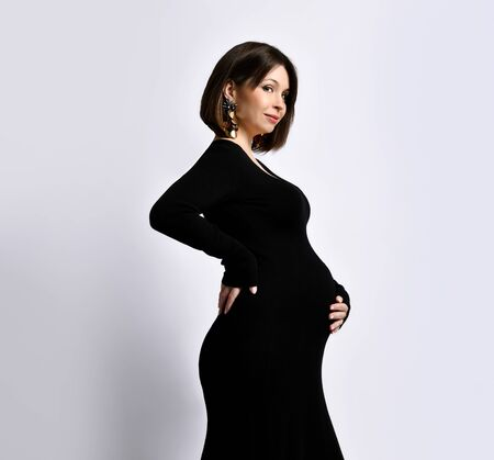pregnant woman in black tight dress and massive earrings. She put hand on her belly, posing sideways isolated on white. Family, maternity, preparation and expectation. Close up, copy space