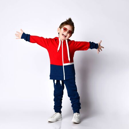 Little blond kid in blue and red tracksuit, sneakers. Smiling, spread his hands, posing isolated on white studio background. Childhood, fashion, advertising and sport concept. Full length, copy space