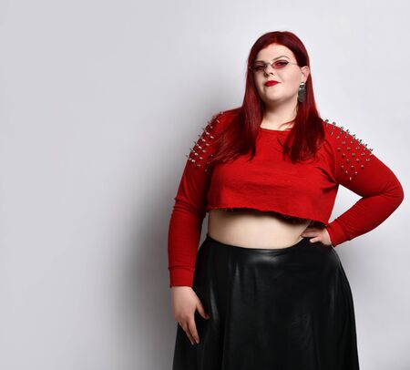 fat redhead lady in a red studded top, black leather skirt, sunglasses and earrings. She smiles, put her hand on her waist, posing isolated on a white background. Fashion Style. Close copy space