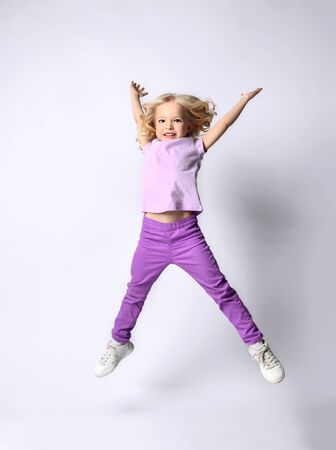 Little blonde curly kid dressed in purple blouse and pants, white sneakers. She is smiling while jumping up with raised hands, posing isolated on white. Childhood, fashion. Full length, copy space Zdjęcie Seryjne