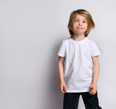 Little blond bro in black and white casual wear. He is smiling, posing on a white background. Childhood, fashion, advertising. Close copy space