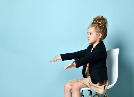 Curly little lady in a beige dress, a black jacket and boots. She extended her arms forward while sitting in a high chair against a blue background. Close, copy space, side view. Zdjęcie Seryjne