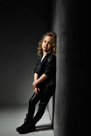 Little blonde curly kid in black leather jacket, pants and boots. She is standing leaning on gray wall in twilight of dark studio. Childhood, fashion, advertising. Full length, copy space, side view Zdjęcie Seryjne