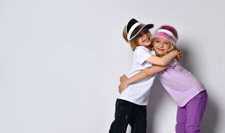 Little blonde female and male in colorful casual clothes and sun visors. They smiling, hugging each other, posing isolated on white background. Childhood, fashion, advertising. Close up, copy space