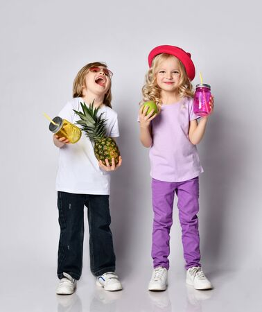 Children in colorful casual clothes, sunglasses, hat. Laughing, holding yellow and pink cocktail bottles, apple, pineapple. Posing isolated on white. Childhood, juicy fruits. Full length, copy space