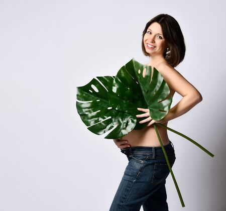 Brunette pregnant girl in jeans, naked to the waist. Smiling, covering chest and belly by two big green leaves, posing sideways isolated on white. Family, maternity, expectation. Close up, copy space