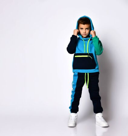 Little brunette child in colorful sport suit and sneakers. He has put his hood on while posing isolated on white studio background. Childhood, fashion, advertising. Full length, copy space Zdjęcie Seryjne