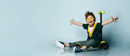 Little brunet child in colorful t-shirt, yellow sunglasses, gray jeans and sneakers. Smiling, spreading hands, sitting on kick scooter against blue background. Childhood, sport. Close up, copy space Zdjęcie Seryjne