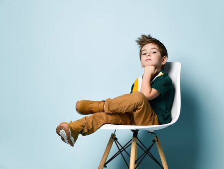 Little brunette kid in colorful t-shirt, brown pants and sneakers. Smiling, propping his chin by fist, sitting on white chair against blue studio background. Childhood, fashion. Close up, copy space