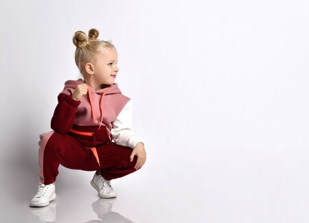 Little blonde kid with buns hairstyle, in colorful tracksuit, sneakers. She smiling, squatting, showing fist, posing isolated on white. Childhood, fashion, advertising and sport. Close up, copy space Zdjęcie Seryjne