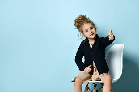 Cute little business girl in stylish black jacket ang beige dress sits in office chair showing thumb up with smile and holding another hand on waist. Studio shot isolated on blue. Fashion, childhood