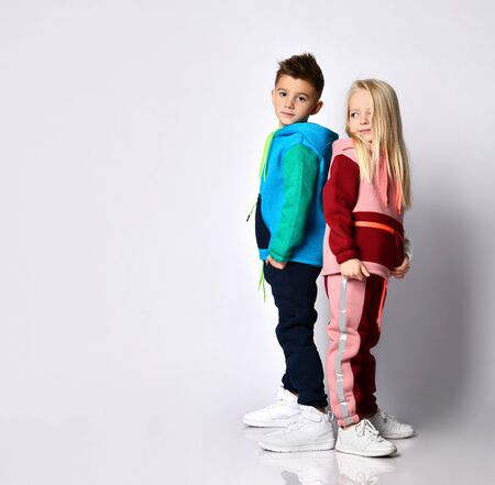 Dark haired boy and blonde girl in stylish jym suits standing back to back. Children athletes, sportswear fashion , togetherness, loving brother and sister. Portrait isolated on light grey, copy space