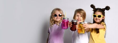 Little male and females in sunglasses, colorful casual clothes. They showing cocktail bottles and smiling while posing isolated on white studio background. Childhood, fashion. Full length, copy space