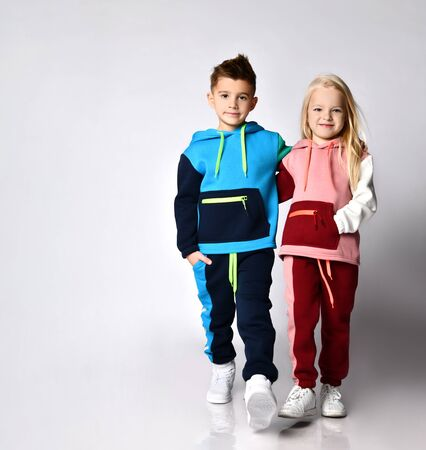 Little boy and girl in bright sportsuits walking forward hand in hand. Young athletes, being stylish, friendship, loving brother and sister. Full length portrait isolated on light grey, copy space