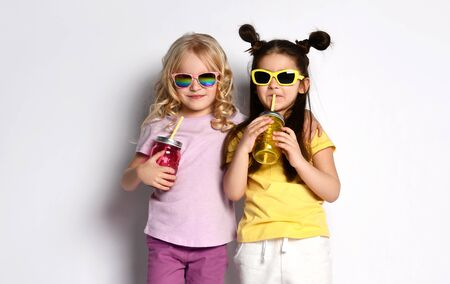 Two little gorgeous friends in sunglasses, colorful casual clothes. They holding cocktail bottles, hugging, showing tongues, posing isolated on white. Childhood, fashion. Full length, copy space