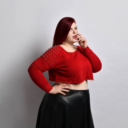 Overweight redhead woman in red spiked top, black leather skirt and earrings. She is touching her face, put hand on waist, posing sideways isolated on white. Fashion and style. Close up, copy space