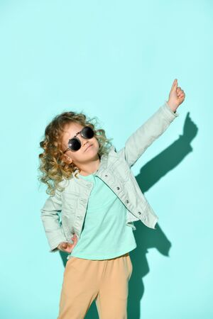 Cute little curly girl with black non-transparent glasses on face stands raising one hand and pointing two fingers up Studio shot isolated on turquoise. Casual style, fashion for children, childhood Zdjęcie Seryjne