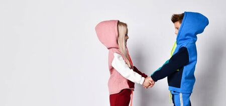 Little kids, brother and sister, in hoods, colorful tracksuits . They holding hands, posing sideways isolated on white. Childhood, fashion, advertising and sport. Full length, copy space