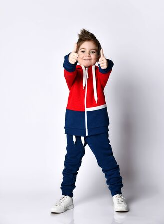 Little blond child in blue and red tracksuit, sneakers. Smiling, showing thumbs up, posing isolated on white background. Childhood, fashion, advertising and sport concept. Full length, copy space
