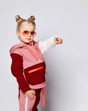 Little blonde model with buns hairstyle, in sunglasses and colorful sport suit. She pointing at you by her forefinger, posing isolated on white. Childhood, fashion, advertising. Close up, copy space Zdjęcie Seryjne