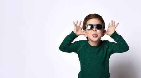Little male in sunglasses and green jumper. He is fooling around and showing his tongue, posing isolated on white studio background. Childhood, fashion, advertising. Close up, copy space