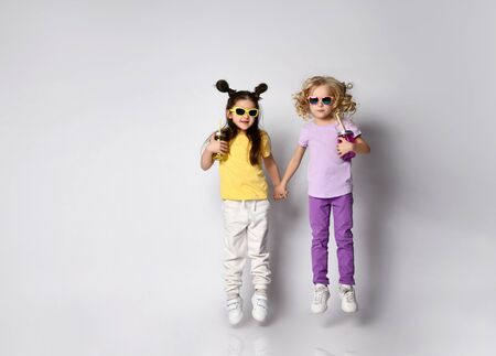Two little gorgeous kids in sunglasses, colorful casual clothes. Girls holding hands and cocktail bottles, jumping up, posing isolated on white background. Childhood, fashion. Full length, copy space
